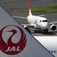 Plane facts: A Japan Airlines Co. jetliner taxis near other JAL jets parked at Narita International Airport on Aug. 3. | BLOOMBERG