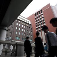 Cost-cutting: People pass the Nomura Holdings Inc. headquarters in Tokyo on July 25. | BLOOMBERG