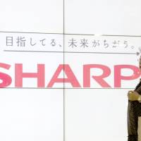 Eye to eye: A woman passes a liquid crystal display monitor showing the Sharp Corp. logo in Tokyo on Aug. 2. The catchline says: 'We are aiming for a different future.' | BLOOMBERG