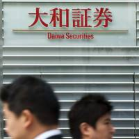 Cost-cutting blur: People walk past the building housing Daiwa Securities Group Inc.'s headquarters in Tokyo last year.   BLOOMBERG