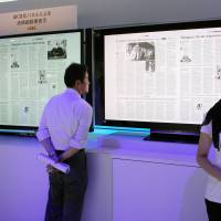 The last word in TV tech: A visitor at the CEATEC Japan 2012 high-tech exhibition reads a newspaper on Sony Corp.'s new 4K liquid crystal display TV set in Makuhari Messe in Chiba Prefecture on Tuesday. | BLOOMBERG