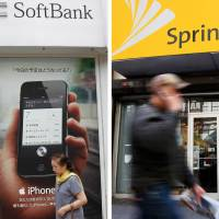 Acquisition target: A woman walks by a SoftBank shop in  Tokyo on April 26 while a man walks past a Sprint store (right) in 2010 in New  York. | AP