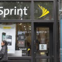 Soon under new management?: A woman passes a Sprint Nextel Corp. shop in New York in April.   BLOOMBERG