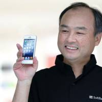 Betting big: Masayoshi Son, chairman and chief executive officer of Softbank Corp., shows off an Apple iPhone 5 during its launch in  Tokyo on Sept. 21. | BLOOMBERG