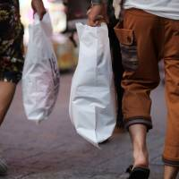 Left holding the bag: Shoppers make the rounds in Tokyo on Aug. 13. | BLOOMBERG