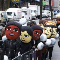 Game faces: People dressed as video game characters line up at Nintendo Co.'s flagship Nintendo World Store in New York as the firm's new Wii U console hit the U.S. market Sunday. | NINTENDO/AP