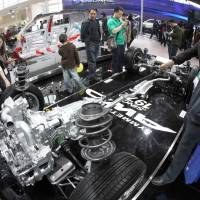 Tech from outside: Visitors view a model of a flat engine at the Fuji Heavy Industries Ltd. booth at the Beijing Auto Show on April 24, 2010. | BLOOMBERG