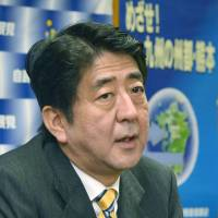 Applying pressure: Liberal Democratic Party President Shinzo Abe faces reporters Saturday in the city of Kumamoto. | KYODO