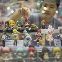 Look out behind you: A man reaches for a miniature 'anime' character in a display booth at the 21st Anime Expo 2012 last June in Los Angeles. | BLOOMBERG