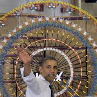 Economic might: President Barack Obama waves after speaking at a toy manufacturer in Hatfield, Pennsylvania, in November. The U.S. economy is riding a wave of successes after last month's jobless rate fell to the lowest since 2008 and the stock market rose to a record high. | AP