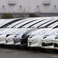 Marching orders: Honda Motor Co. vehicles await shipment in the port of Yokohama in January. Business sentiment at large companies is believed to have improved in the first quarter of 2013 thanks to a weaker yen and higher stock prices, the government said Tuesday. | BLOOMBERG