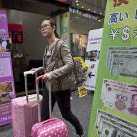 Cashing out: A tourist walks past a currency exchange store in Seoul's Myeongdong shopping district in October.   BLOOMBERG