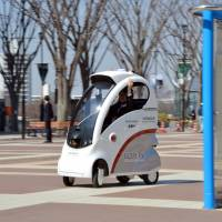 One-seater: Hitachi Ltd.'s new Robot for Personal Intelligent Transportation System goes on a test run in Tsukuba, Ibaraki Prefecture, on Tuesday. The ROPITS can be programmed to pick up and drop off a passenger. | AFP-JIJI