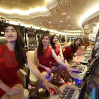 Roll the dice: Casino models pose at the slot machines during a media tour of the Philippines' new Solaire Casino on Thursday in suburban Pasay. Michael French, chief operating officer of Solaire Resort and Casino, said studies not commissioned by his company project Filipino gaming revenue could rise from $1.9 billion to $6 billion, equivalent to Singapore's revenue, in about five years. | AP