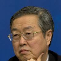 Zhou Xiaochuan, governor of the People's Bank of China, attends a press conference Wednesday. He said the central bank will maintain its current monetary policies. | AP