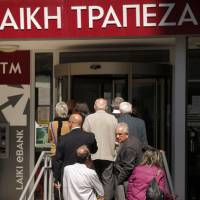 ?100,000 and hosed: People line up outside a Laiki branch in Nicosia on Friday as Cyprus reopened its banks for a second day under Draconian capital controls. | AFP-JIJI