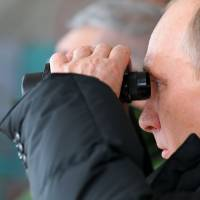 Appeased: Russian President Vladimir Putin watches a military exercise in the Black Sea resort of Anapa on Friday. | AP