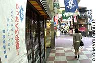 Signs like the one on the left warning passersby of purse-snatchers are springing up all over Osaka, the nation's purse-snatching capital.