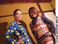 Volunteer model Sasha (left) sports a shirt made from a used tablecloth as colleague Masami wears a vest and mini-skirt made from a used blanket.