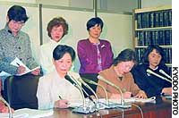 Female employees of Nomura Securities Co. and their lawyers talk to reporters at the Tokyo District Court.