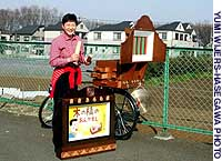 'Kamishibai' performer Kirara displays a bicycle-mounted stage and a larger set that her group uses for performances.