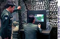 A GSDF official demonstrates a game at the information center in Tokyo.