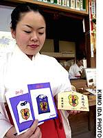 A shrine maiden displays some of the famous charms.
