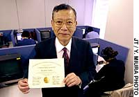 Masahiko Tanabe shows off the U.S. CPA degree that he earned at the age of 70.