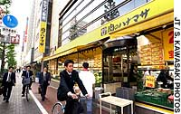Pedestrians pass an outlet of the Hanamasa wholesale supermarket chain at a busy intersection in Tokyo's Chuo Ward.