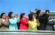 Fans of 'Dear Leader' -- Women wearing the traditional chogori dress, applaud Kim Jong Il at a military march-past in Pyongyang last week.