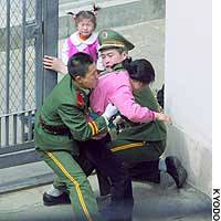 A woman believed to be a North Korean is apprehended at the gate of the Japanese Consulate in Shenyang, China.
