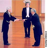 Emperor Akihito bestows the Grand Cordon of the Order of the Rising Sun on Shoichiro Toyoda, former chairman of Toyota Motar Corp. and Keidanren, at the Imperial Palace as Prime Minister Junichiro Koizumi looks on.