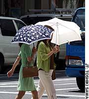 Two women use parasols to protect themselves from the Tokyo sun as they walk in the Nihonbashi district.