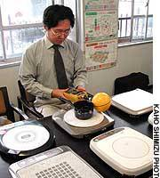 Takenori Ueda of the Japan Offspring Foundation gauges the radiation from an induction-heating electric stove at the foundation's office in Chiyoda Ward, Tokyo.