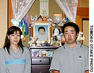 Shinobu and Shinya Ishii flank a portrait of their son, Mahrio, who allegedly died of SIDS at a hospital in Funabashi, Chiba Prefecture.