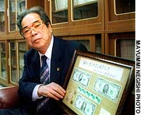 Matsusho Miyazato, former deputy chief of the Ryukyu Government under U.S. rule, displays marked dollars Okinawans could exchange at the time of the 1972 reversion.
