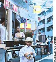 A Pakistani boy smiles in front of a curry stall run by local Muslims at a community festival Aug. 29 in the Minami Otsuka district of northern Tokyo.