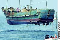 A suspected North Korean spy ship is lifted from the sea.