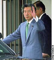 Prime Minister Junichiro Koizumi waves to reporters as he leaves his temporary residence in Shinagawa Ward, Tokyo.