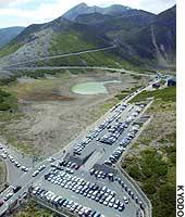 Tourist buses and taxis fill a parking lot near the summit of Mount Norikura in the Japan Alps.