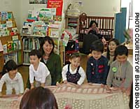 Kids play with cloth during an exercise at bi-no bi-no, a Yokohama-based 'drop-in center' for mothers and children.
