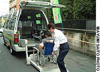 Employees of taxi operator Suginami Transportation demonstrate how a passenger in a wheelchair is lifted aboard one of its so-called nursing taxis.