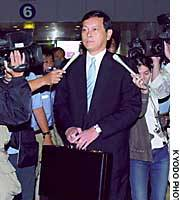 Akitaka Saiki, deputy director general of the Foreign Ministry's Asian and Oceanian Affairs Bureau, is surrounded by reporters as he leaves Beijing airport for Pyongyang.