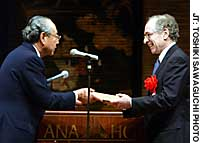 Gerald Curtis, a U.S. political scientist, receives an award from Hiroaki Fujii, president of the Japan Foundation, during a presentation ceremony Friday in Tokyo.