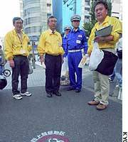 Officials in Tokyo's Chiyoda Ward patrol a ward street where smoking has been banned.