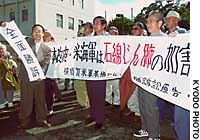Supporters of plaintiffs in a lung disease case hold banners in front of the Yokohama District Court's Yokosuka branch.