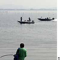 Sportfishermen angle for black bass on Lake Biwa. A proposed ordinance would ban the practice of catching and then releasing foreign species there.