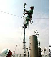 Workers install a measuring device atop a metropolitan government facility in Koto Ward in late July to monitor the effects of urban warming.