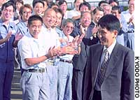 Koichi Tanaka (right), an employee of Shimadzu Corp., is welcomed by colleagues at the company's head office in Nakakyo Ward, Kyoto, to celebrate his winning of the Nobel Prize in chemistry.