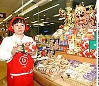 Junko Saito, a clerk at Aomori Hokusai-kan, displays apple cakes, canned sea urchin soup and 'awabi' abalone at the prefectural shop in Tokyo's Iidabashi district.
